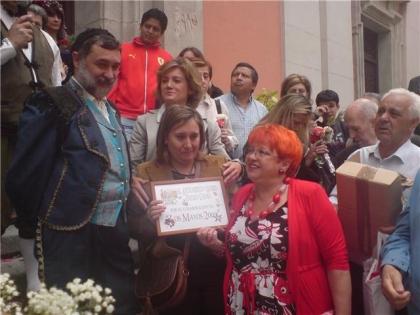 Carmen Cano, vocal vecina socialista, entrega uno de los premios.